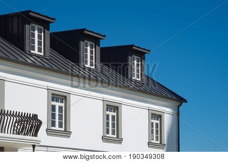 View on top of residential house facade against blue sky real estate concept