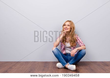 Thoughtful Young Cute Smiling Woman Sitting On The Floor And Thinking About Her Dreams