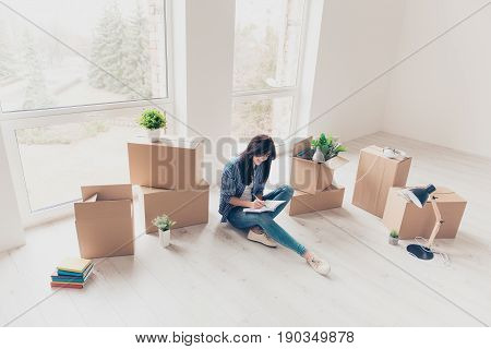Home, Sweet Home! Young Girl In Casual Clothes Is Sitting With Crossed Legs On The Floor Of Her New