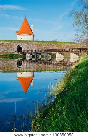 Kuressaare castle tower with bridge over the moat against blue sky. Water with reflections on foreground.