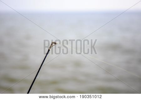 closeup to fishing rod hook at sea or ocean.