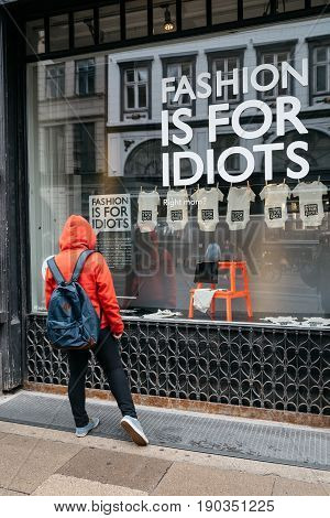 Copenhagen Denmark - August 10 2016. Young woman wearing casual clothing looking at store window in Copenhagen with the words Fashion is for Idiots