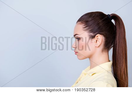 Close Up Cropped Profile Portrait Of Young Lady In Yellow Tshirt With Ponytail, Serious Face On Pure