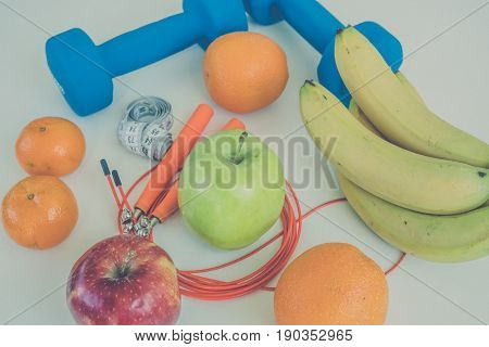 The concept of a healthy diet. Dumbbells, rope, bananas, oranges, roulette, oranges, red apple, green apple, orange juice on a white table. healthy lifestyle. sport. Fitness diet. View from above