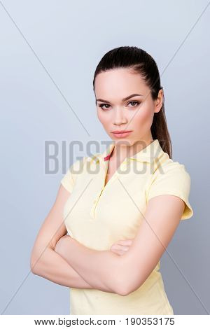 Portrait Of Serious Young Freelancer Brunette Lady, She Stands With Crossed Hands In Yellow Tshirt O
