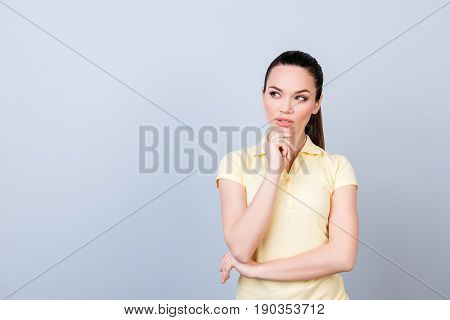 Portrait Of Serious Young Freelancer Brunette Lady, She Stands In Yellow Tshirt On Pure Light Backgr