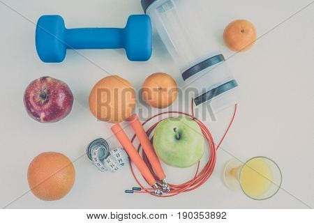 healthy eating concept. Dumbbells, skipping rope, shaker, bananas, oranges, measuring tape waist, oranges, red apple, green apple, orange juice on a white table. healthy lifestyle. sport. Fitness diet. view from above.