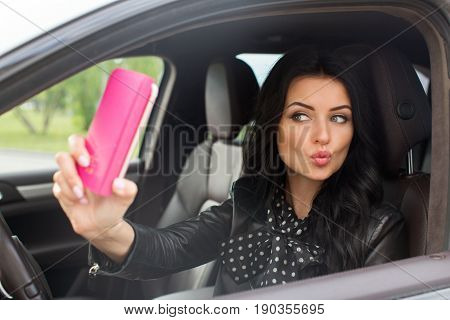 Beautiful brunette woman doing selfie in the car. Lips young woman taking selfie picture with smart phone camera outdoors in car