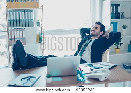 Glad Young Businessman Is Resting In His Office With Feet Up On Table. He Is Smiling, Wearing Formal