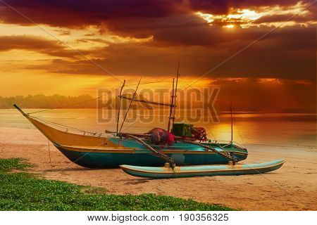 Sandy beach with colorful fishing boats at sunset. Sri Lanka Island.