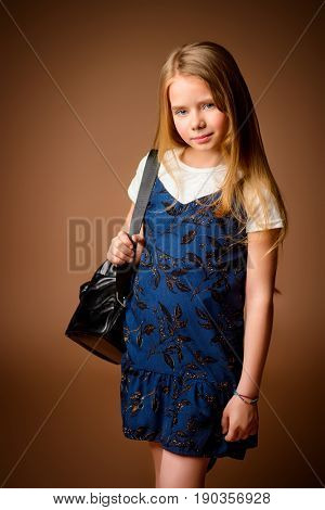 Children's fashion. Cute eight year old girl with long blonde hair posing in summer dress and a bag. Studio shot.