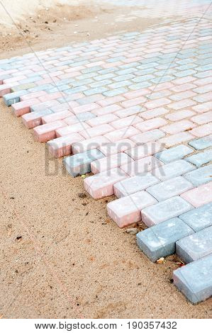 Colored brick paving stones in construction process. Outdoors colored vertical image.