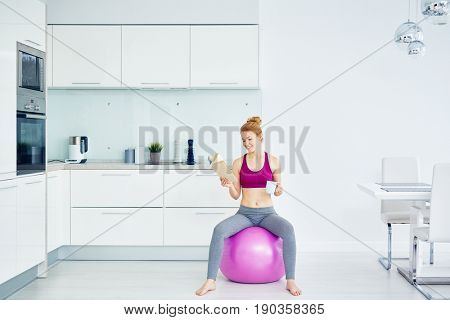 Portrait of smiling  red haired woman doing  exercises at home, sitting on fitness ball and reading  book