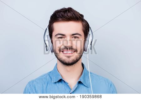 Happy Young Cute Guy Is Listening To The Music In Big White Headphones On Light Blue Background