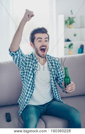 Vertical Portrait Of Happy Man In Casual Checkered Shirt And Jeans Drinking Beer At Home And Celebra