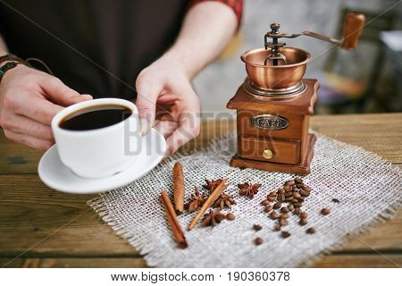 Closeup shot of barista holding cup of perfect dark espresso next to  antique mill grinder