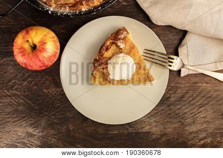 An overhead photo of a piece of a homemade apple pie with a scoop of ice cream, with the rest of the pie in a skillet, and an apple, with a place for text