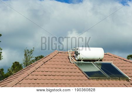 The solar water heater at the rooftop of the house with the cloud.The environment conservation concept.