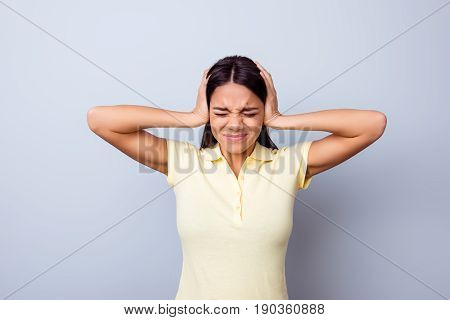 Stop it! Young mulatto girl is covering her ears because of noises she is stressed and tired