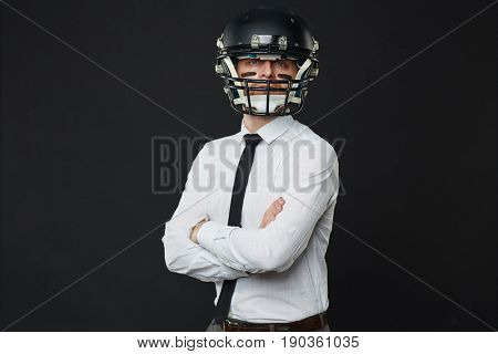 Waist up portrait of confident businessman wearing American football helmet standing cross-armed against black background and looking at camer
