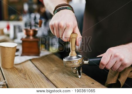 Closeup shot of barista working in coffee shop: pressing fresh grains with tamper