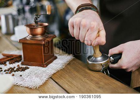Closeup shot of barista working in coffee shop: pressing fresh grains in portafilter