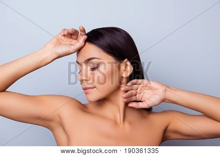 Beauty concept. Young pretty latin mulatto lady is touching gently her attractive healthy bronze skin