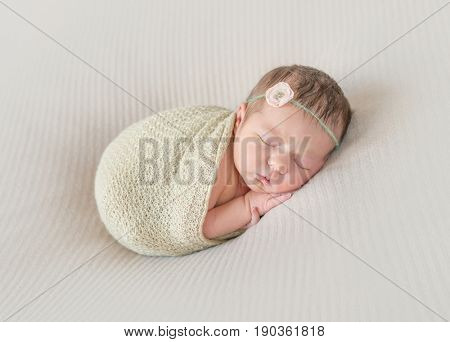 Adorable kid napping wrapped with a scarf, arm hanging out of it, sleeping tight