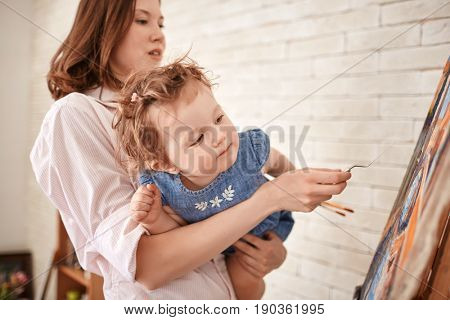 Portrait of young woman painting picture in art studio with curious baby girl in arms
