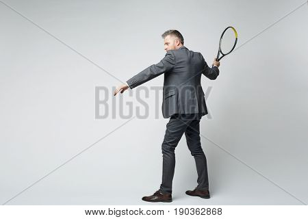 Full length portrait of middle aged businessman in suit hitting shot with tennis racquet against grey background