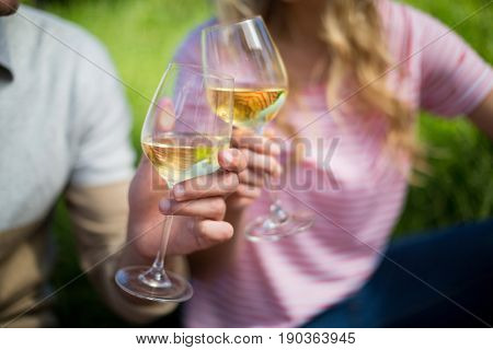 Close up of couple toasting white wine glasses