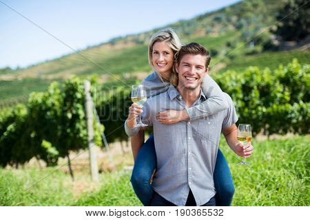 Portrait of happy young couple holding wineglasses while piggybacking at vineyard
