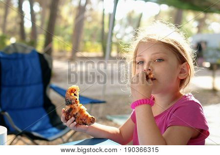 Little caucasian girl (elementary age) having a breakfast outdoor in the summer sunny morning. Summer camping active recreation and touristic concept.