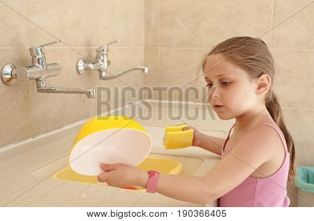 Little caucasian girl (elementary age) washing a dishes outdoor in the camping sink. Summer camping active recreation touristic and education concept.