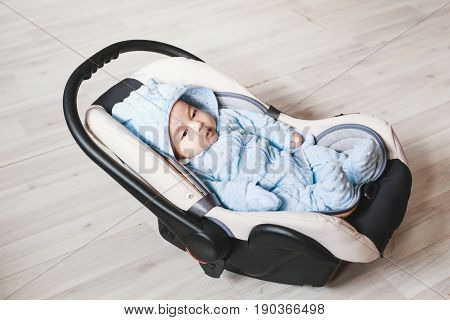 Portrait of cute baby boy sitting in car seat. Child transportation safety.