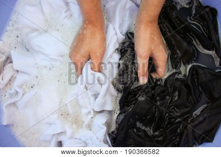 Female hand wash black and white clothes in same basin.