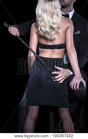 Man in tux with whip grab woman lover ass by hand isolated