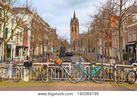 Hague, Netherlands - April 6, 2016: City street, church clock tower and canal view with bicycle in Hague, Holland