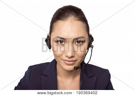 Smiling young asian call center operator in headset looking at camera
