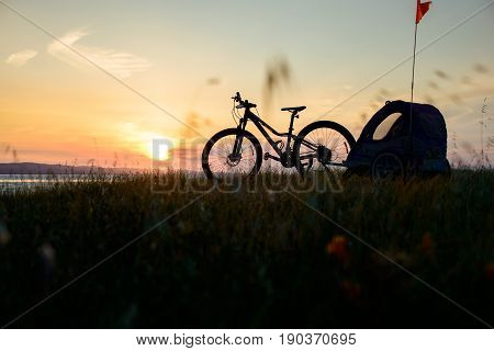 Silhouette of bicycle with child carrier at sunset, high on grass hill, bay in the distance.