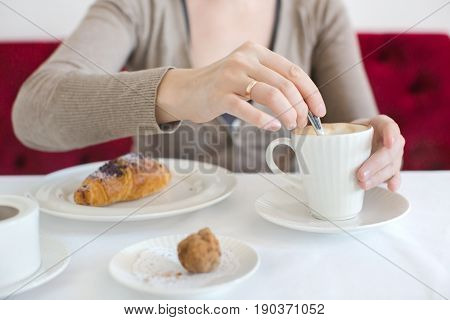 Woman stirs sugar in cappuccino next to lies croissant. Anonymous casual woman sitting at table with coffee and croissant.