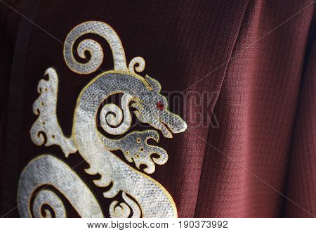 Asian Chinese Dragon Made Of Fish Skin Crafted On Vinous Fabric. Decorative Dragon With Red Eye Made