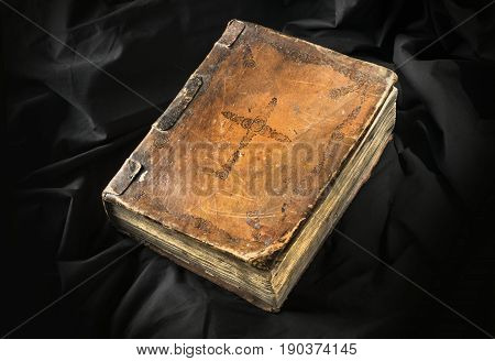Old Book On Black Background. Ancient Christian Bible. Antique Holy Scripture Book. Cross On Bible C