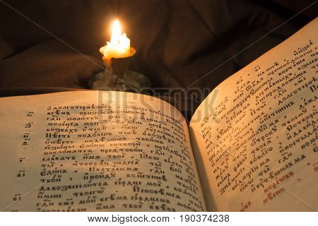 Open Book With Candle Soft Light Pouring On Text. Reading Of Opened Book Educate Reader. Ancient Bib