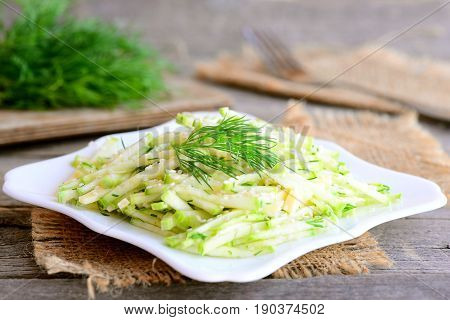 Fresh zucchini and cheese salad with lemon vinaigrette. Home salad with fresh zucchini, cheese and dill on a plate. Simple and quick vegetarian salad. Rustic style. Closeup