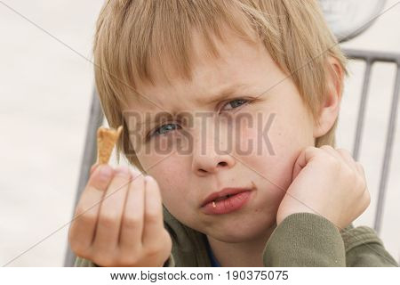 Boy eating ice cream who present disappointment because of that I ate it asks for the next
