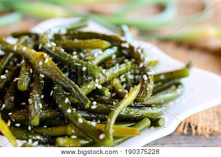Fried garlic arrows with spices mixture and sesame seeds. Savoury green garlic arrows on a white plate. Quick, cheap and tasty meat free recipe. Closeup