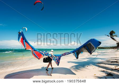 Kite surfing. Kite surfer walking on the beach with a kite in hand. Wide angle. Active extreme sport lifestyle. Bulabog Boracay Philippines.