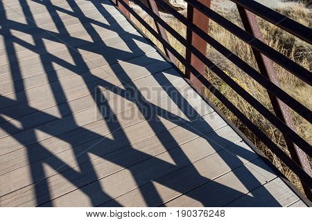 Shadow patterns of wooden and handrail bridge.
