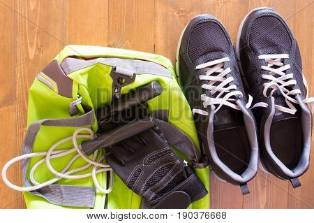 Green bag for sporting things on a wooden background and shoes